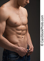 Close up of sexy fit man undressing. Standing with naked torso over dark background and unbuttoning jeans