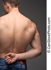 Close up of sexy male nude muscular back. Standing in jeans isolated over grey background