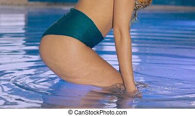 Close up of sexy wet girl's buttocks posing in bikini in basin. Slowly