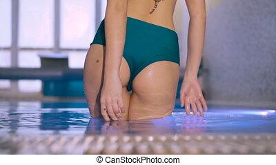 Close up of sexy wet girl's buttocks posing in bikini in basin 4K