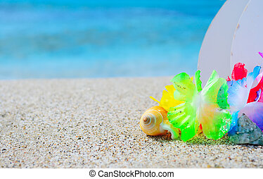 shell and hawaiian necklace on the sand