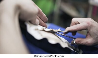 Close up of shoemaker cutting leather with scissors