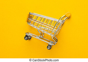 shopping trolley on yellow background - close-up of shopping...