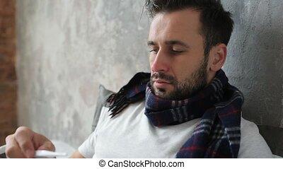Close up of sick man checking temperature