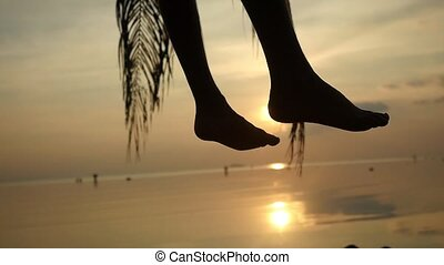 Close up of silhouette of male legs. Young man sits on a palm tree waving legs through the sun at tropical beach during beautiful sunset. Slow motion. 1920x1080