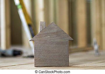 Close-up of simple small brown model house on blurred building tools background. Construction, building and investments in real estate, property and ownership of dream home concept.
