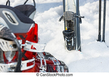 Close up of ski latch near red and gray boots laying in fluffy snow in a ski-resort