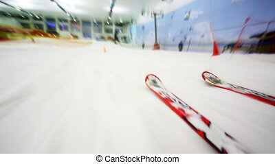 close-up of skis fast going down hill in big sport center perambulate barriers, side view