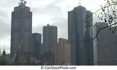 Medium close-up daytime, low angle tracking focus still shot of office building skyscrapers against a cloudy bright sky, Melbourne, Australia