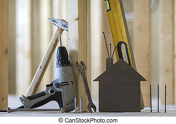 Close-up of small brown model house and building tools on wooden planks in unfinished room under construction background. Investments in real estate, property and ownership of dream home concept.