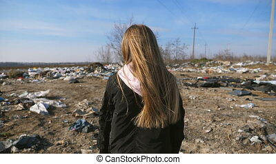 Close up of small female kid with long blonde hair walks on dirty garbage dump. Little girl goes over the trash at junkyard. Concept of environmental pollution problem. Rear view Slow motion.