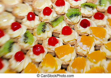 close-up of small fruit tarts arranged in rows depending on the fruit, pineapple, kiwi, cherry and orange