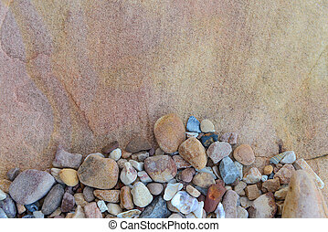 Close up of small rounded rocks on boulder background