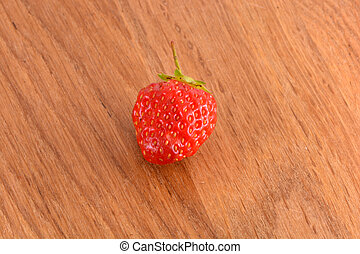 close up of small strawberry on wood