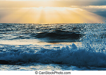 Close up of small waves under a shining sun at sunset