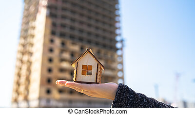 Close up of small wooden house in woman's hand on background of house under construction. Concept of purchasing new apartment.