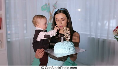 Close-up of small year old boy eating cake with his hands and feeding his mother