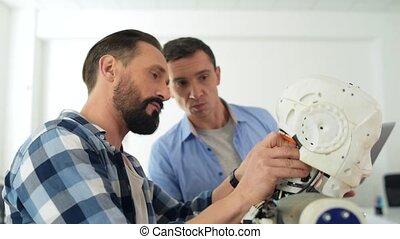 Close up of smart constructors repairing robot head -...