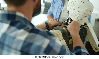 Close up of smart engineers repairing robot construction -...