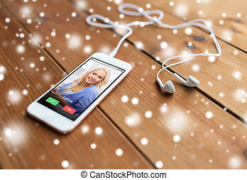 close up of smartphone and earphones on wood