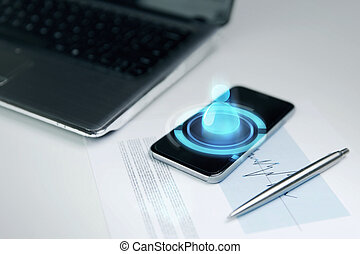 close up of smartphone, laptop and pen on table