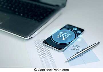 close up of smartphone with shopping cart icon