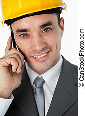 Close up of smiling architect listening to caller against a ...
