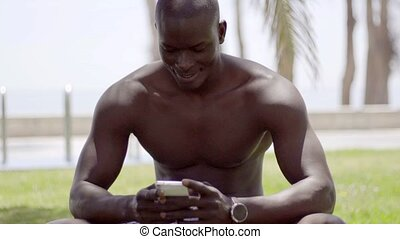 Close up of smiling black man checking his phone