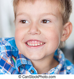 Close up of handsome little boy with a big smile on his face and a twinkle in his eyes