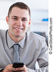Close up of smiling businessman with cellphone in his hands