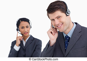 Close up of smiling call center agent with co-worker behind him