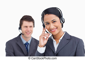 Close up of smiling call center agent with colleague behind her