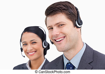 Close up of smiling call center employees against a white...