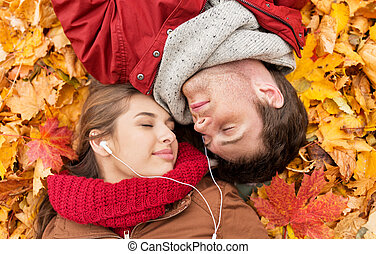 close up of smiling couple lying in autumn park - love, ...