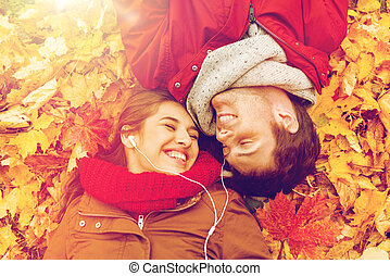 close up of smiling couple lying in autumn park