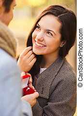 love, relationship, family and people concept - close up of smiling couple with red gift box in autumn park