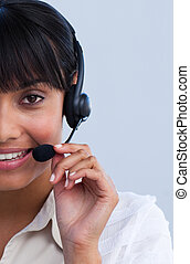 Close-up of smiling ethnic young businesswoman working in a call center