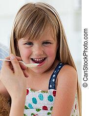 Close-up of smiling girl taking medecine