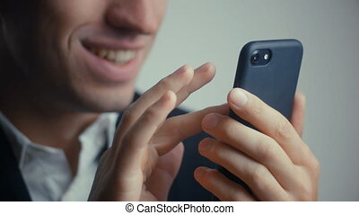 close-up of smiling happy businessman in a suit is using a smartphone. Isolated on white background
