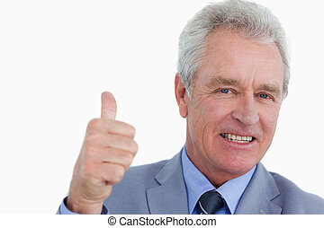 Close up of smiling mature tradesman giving approval against...