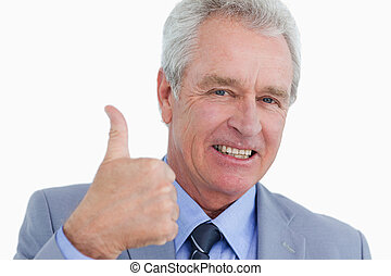 Close up of smiling mature tradesman giving thumb up against...