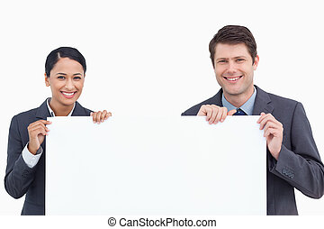 Close up of smiling salesteam holding blank sign