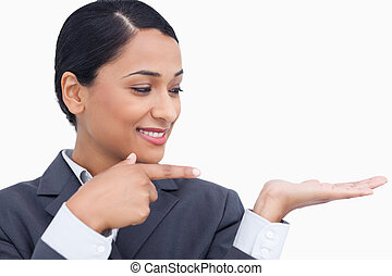 Close up of smiling saleswoman pointing and looking at her palm