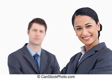 Close up of smiling saleswoman with co-worker behind her