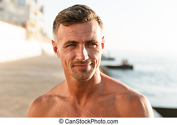 Close up of smiling shirtless sportsman at the beach