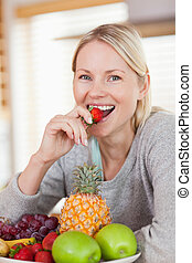 Close up of smiling woman having a strawberry