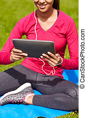 close up of smiling woman with tablet pc outdoors