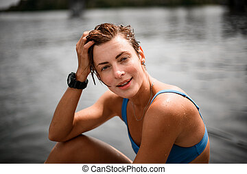 Close-up of smiling woman with wet short hair.
