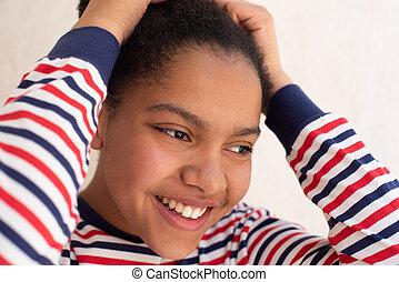 Close up of smiling young african american girl with hands in hair