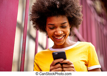 Close up of smiling young african american woman looking at mobile phone outside